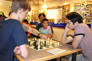 GM Mesgen Amanov reviews Tommy Ulrich's name with Steven Tennant while David Peng and his dad look on.